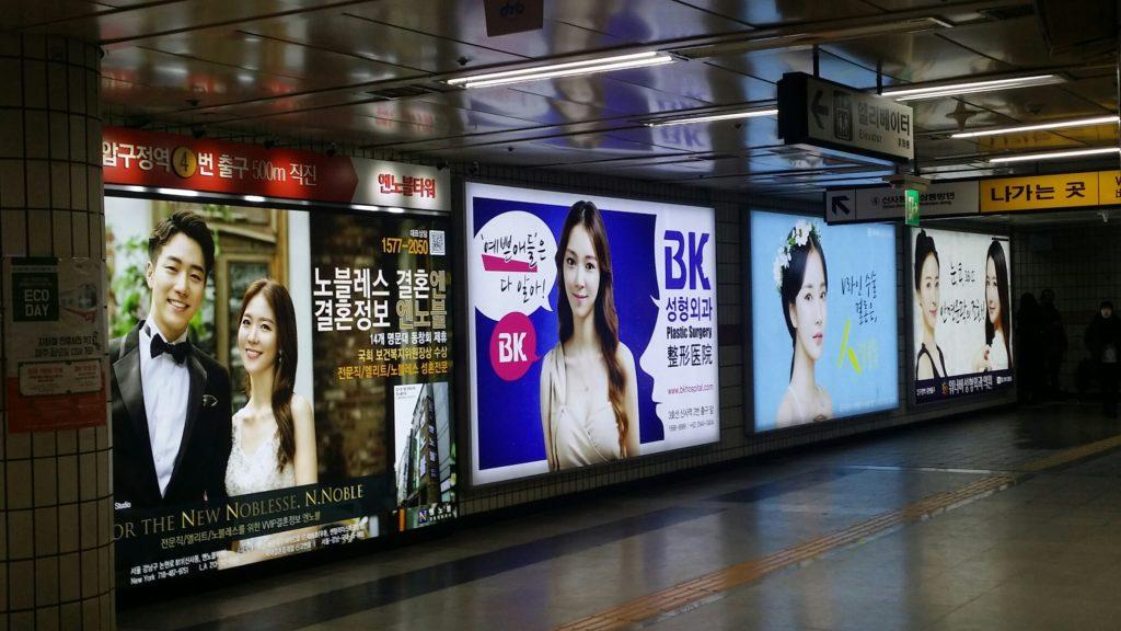 U-Bahnstation Abugegong Station in Seoul mit Werbeanzeigen für Schönheitsoperationen